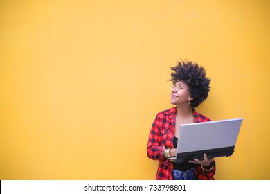 Smart girl using a laptop and looking up on the wall