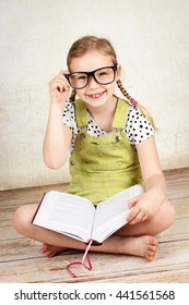 Smart girl wearing glasses and reading a book