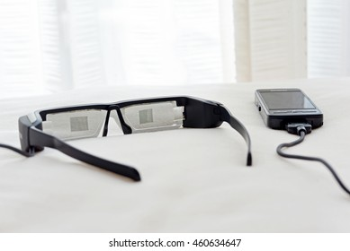 Smart glasses with smart phone on bed. Concept about technology and connected social media everywhere.