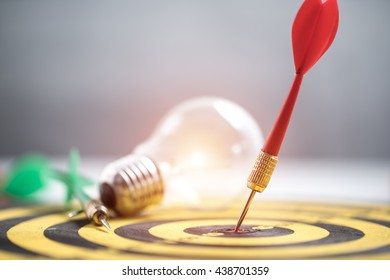 Smart goal setting, dart hit the center of dartboard with light bulb  on background