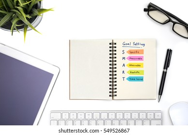 Smart goal setting with notebook, eye glasses, pen, mouse, keyboard, tablet, computer and plant on white office table view from above, Success concept