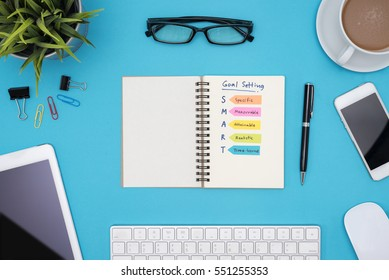 Smart goal setting on notebook with office supplies, computer, eye glasses and coffee cup over blue desk background, Business success concept