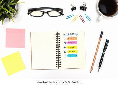 Smart goal setting on spiral notebook with pen, pencil, office supply, eye glasses and coffee cup over white desk table  background, Business success concept
