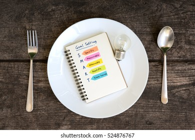 smart goals setting and hand written acronyms definition on the notebook and light bulb in a plate with spoon and fork on grunge table, Business success concept