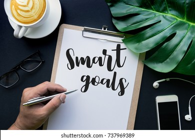 Smart goals text with hand writing on notepaper and accessories laying on black table.business challenge concepts.flat lay/top view