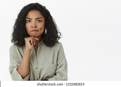 Smart good-looking stylish african american female entrepreneur being concerned and perplexed thinking smirking frowning and holding hand on chin while creating idea or making decision