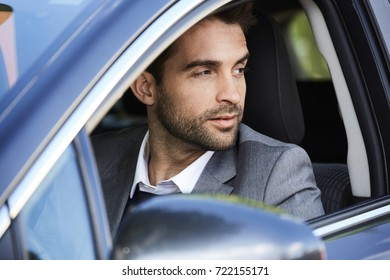 Smart guy in grey driving in car, looking away