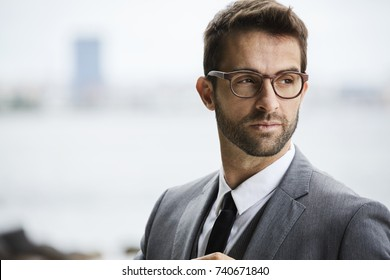 Smart guy in grey suit and glasses, looking away