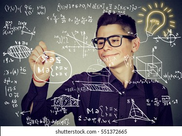 Smart guy writing high school maths and science formulas on blackboard