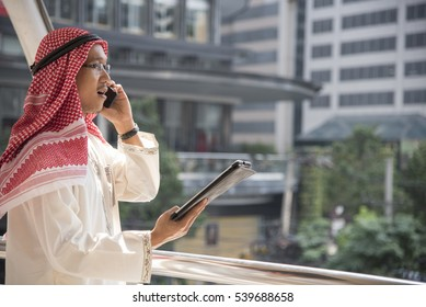 Smart handsome arab businessman using mobile phone in the city.