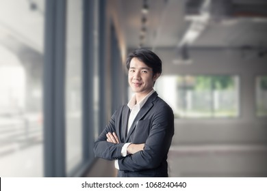 A smart and handsome business man, who is standing beside the windowpane of the office. A clever guy is an executive of company and has more of employees in there, with blurry background.