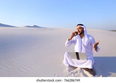 Smart handsome emirate guy businessman prints on computer keyboard and answers incoming phone call from business partner or client, communicates about building in desert. Young Arab smiles and sits on