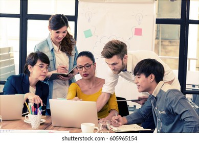 Smart handsome european man business officer explaining internal meeting to his project team in modern office. multi ethnic business person group in casual suit. Project and Business concept.