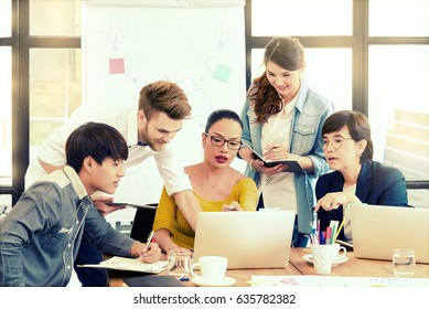 Smart handsome european man business officer explaining internal meeting to his project team in modern office. The multi ethnic business person group in casual suit. Project and Business conc