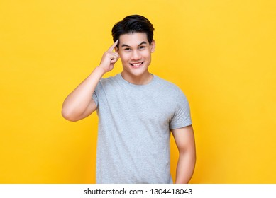 Smart handsome young Asian man thinking with finger on head isolated on colorful yellow background