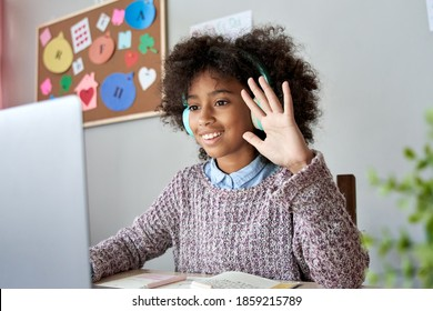 Smart happy african american kid girl wearing headphones waving hand talking with remote web teacher on social distance video conference call elearning class on computer. Children learning at home.