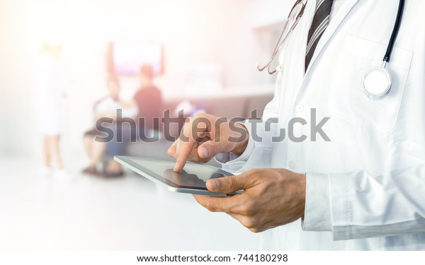 Smart health care internet of things and hospital automation management technology concept with paperless. Doctor with Stethoscope using tablet for remote monitoring to check status of patient.