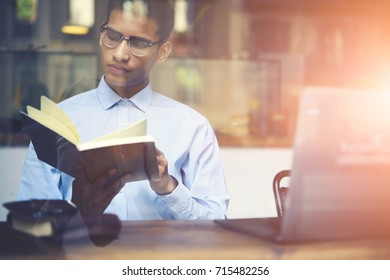 Smart hindu student in eyeglasses preparing for exams with training literature sitting in coffee shop interior.Hipster guy dressed in blue shirt turning pages of book and reading useful information