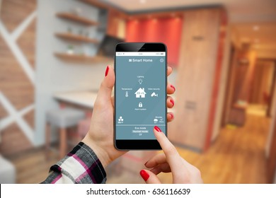 Smart home automation app interface on phone to control house in female hands, with living room interior in background