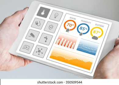 Smart home automation dashboard to control devices and sensors in the house or apartment. Hand holding modern tablet.