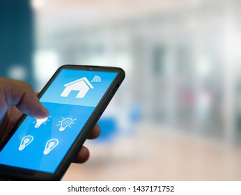 Smart home automation. hands holding smartphone to control the Electrical equipment in the house.