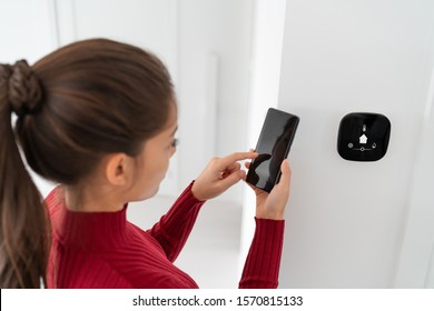 Smart home automation woman using phone app regulating indoor temperature regulation smart house screen system. Domotics technology device changing lighting, climate, appliances.