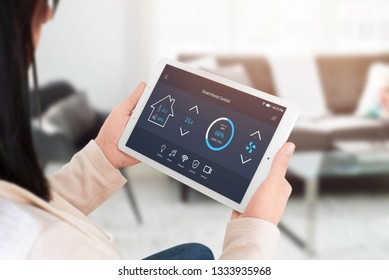 Smart home control app on tablet display in woman hands. Home, living room interior in background.