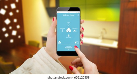 Smart home remote control app in woman hand. Kitchen in background