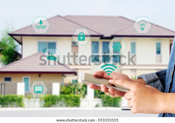 Smart home security system, house automation, Woman hand touch smart phone as mobile device remote control application for tv, thermostat,  electric, computer, smart home, internet of things concept