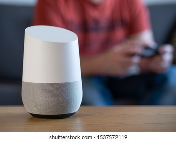 smart home voice activated speaker in lounge with gamer in background