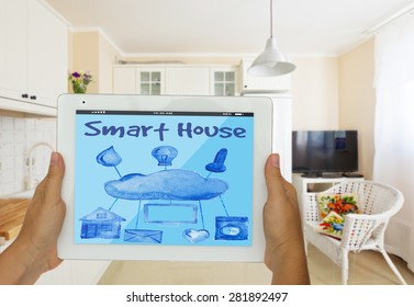 Smart house concept - hands holding tablet with remote control
