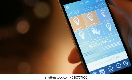 Smart house, home automation, device with App icons. Man uses his smartphone with smarthome app to control the lights of his house.