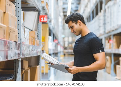 Smart Indian engineer man worker doing stocktaking of product management in cardboard box on shelves in warehouse. Factory physical inventory count.