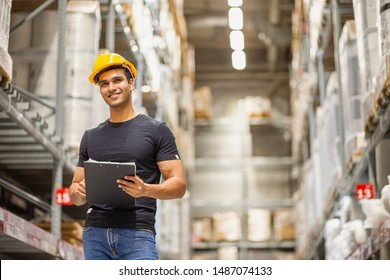 Smart Indian engineer man worker wearing safety helmet doing stocktaking of product management in cardboard box on shelves in warehouse. Factory physical inventory count.