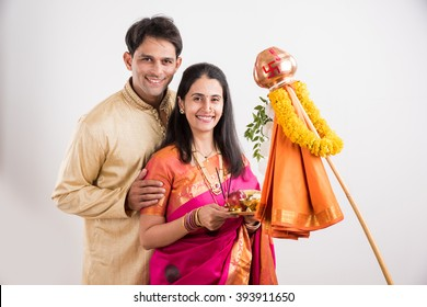 Smart Indian young couple performing Gudi Padwa Puja in traditional cloths & pooja thali. It's a Hindu New Year celebrated across India, showing Gudhi/Dhwaj made up of Kalash, garland, cloth on stick