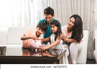 Smart Indian/asian couple teaching importance of saving to kids at home with piggy bank