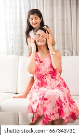 Smart Indian/Asian Mother and Daughter together having fun at home