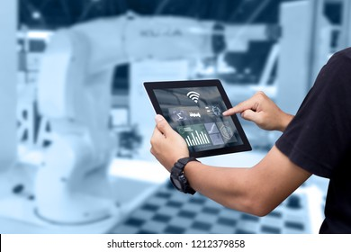Smart industry control concept.Hands holding tablet on blurred automation machine as background