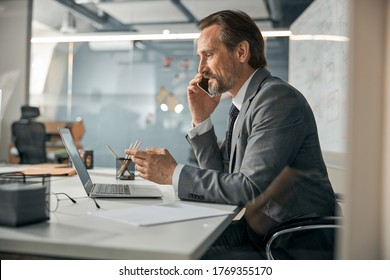 Smart intelligent specialist sitting at the office table and giving recommendation to client