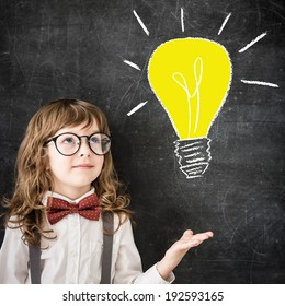 Smart kid in class. Happy child against blackboard. Drawing light bulb. Business idea concept