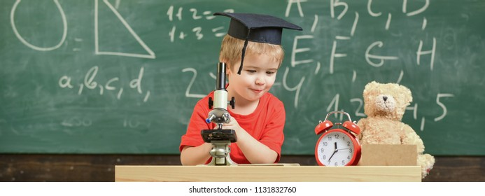 Smart kid concept. Child on happy face holds microscope. First former interested in studying, learning, education. Kid boy in academic cap work with microscope in classroom, chalkboard on background.