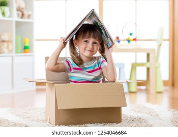 Smart kid girl sitting in cardboard box and holding a book over head as roof