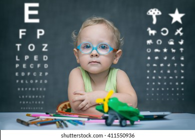 Smart kid sitting at a table with glasses