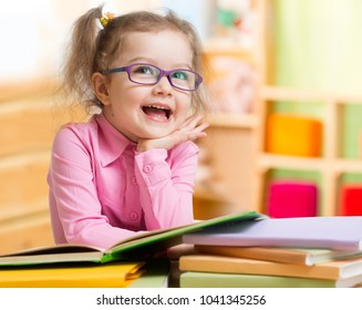 Smart kid in spectacles reading books in her room