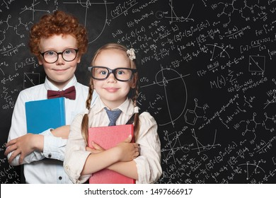 Smart kids portrait. Little girl and boy student holding books and standing against blackboard background with science and maths formulas