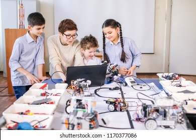 Smart kids with their mother learn programming using laptop at home, science children creativity study concept
