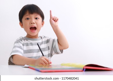 Smart little asian boy having an idea while doing his homework, isolated on white background