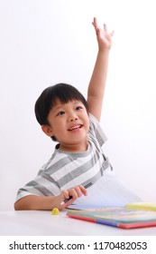 Smart little asian boy putting up his hand in class to answer a question for his teacher, isolated on white background
