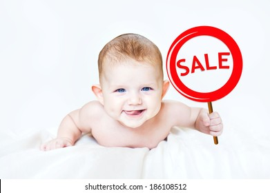 "Smart little boy holding a sign ""SALE"" in the hands. In light background."
