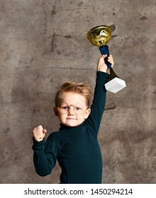 smart little boy in jeans, sweater and glasses celebrates his won gold trophy against the background of a concrete wall. The concept of smart children